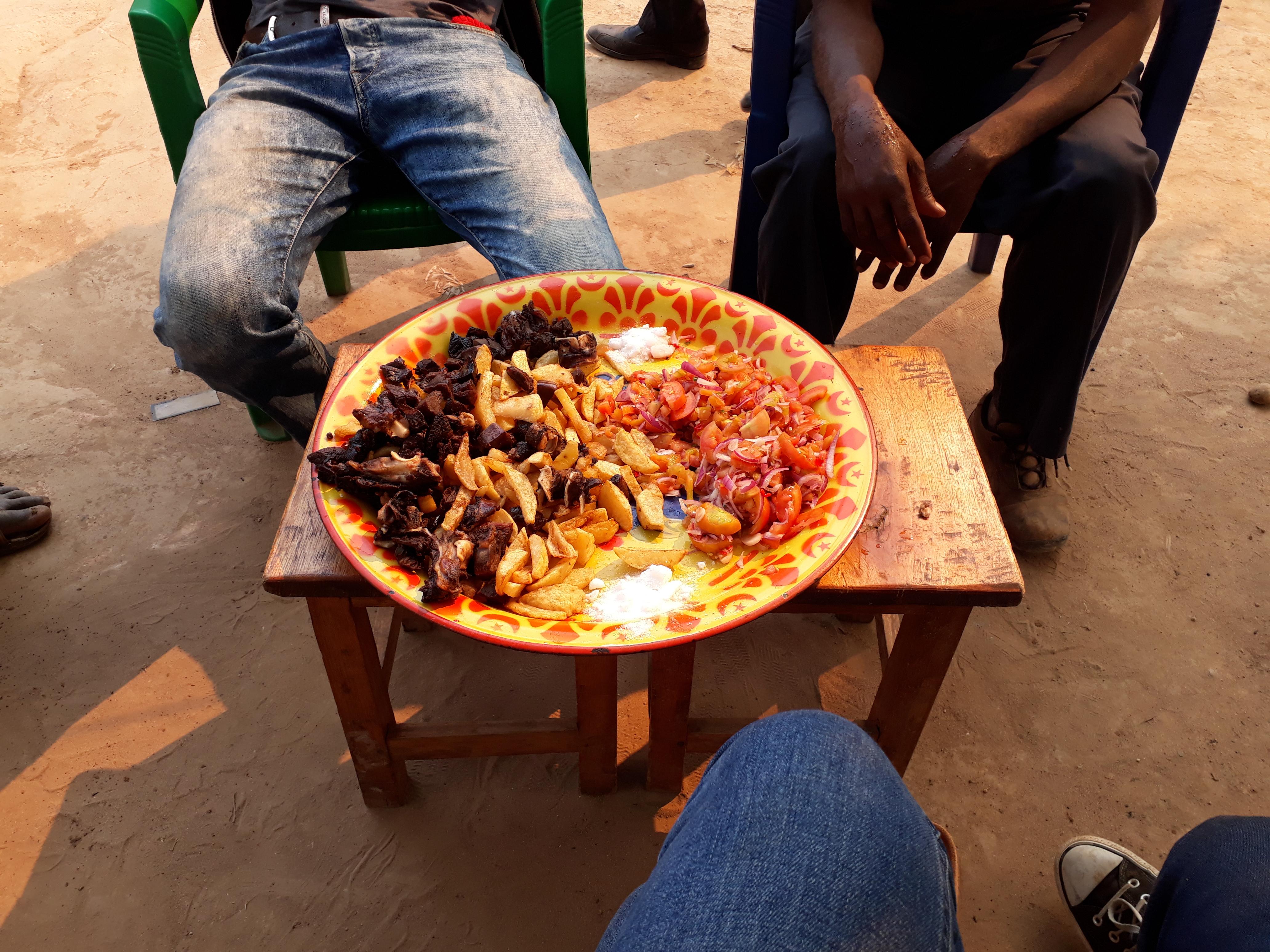 Schweinefleisch, Chipsi und Kachumbari (scharfer Tomatensalat)